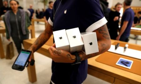 FILE PHOTO: An Apple Store staff shows Apple's new iPhones X after they go on sale at the Apple Store in Regents Street London