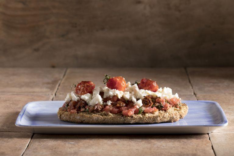 Ντάκος με ψητά ντοματίνια, λιαστή ντομάτα και ξινομυζήθρα | tovima.gr